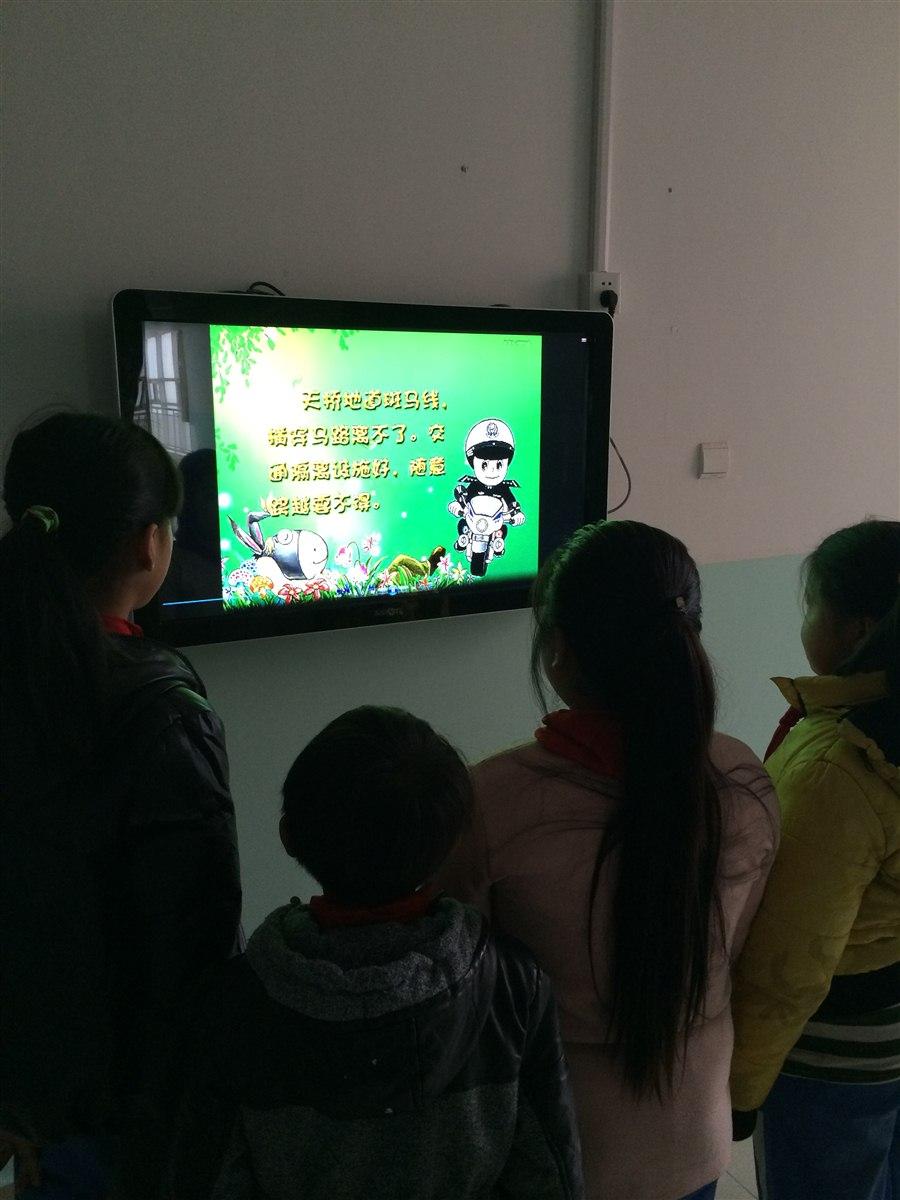图为五年级四班部分同学正在观看交通安全的宣传片